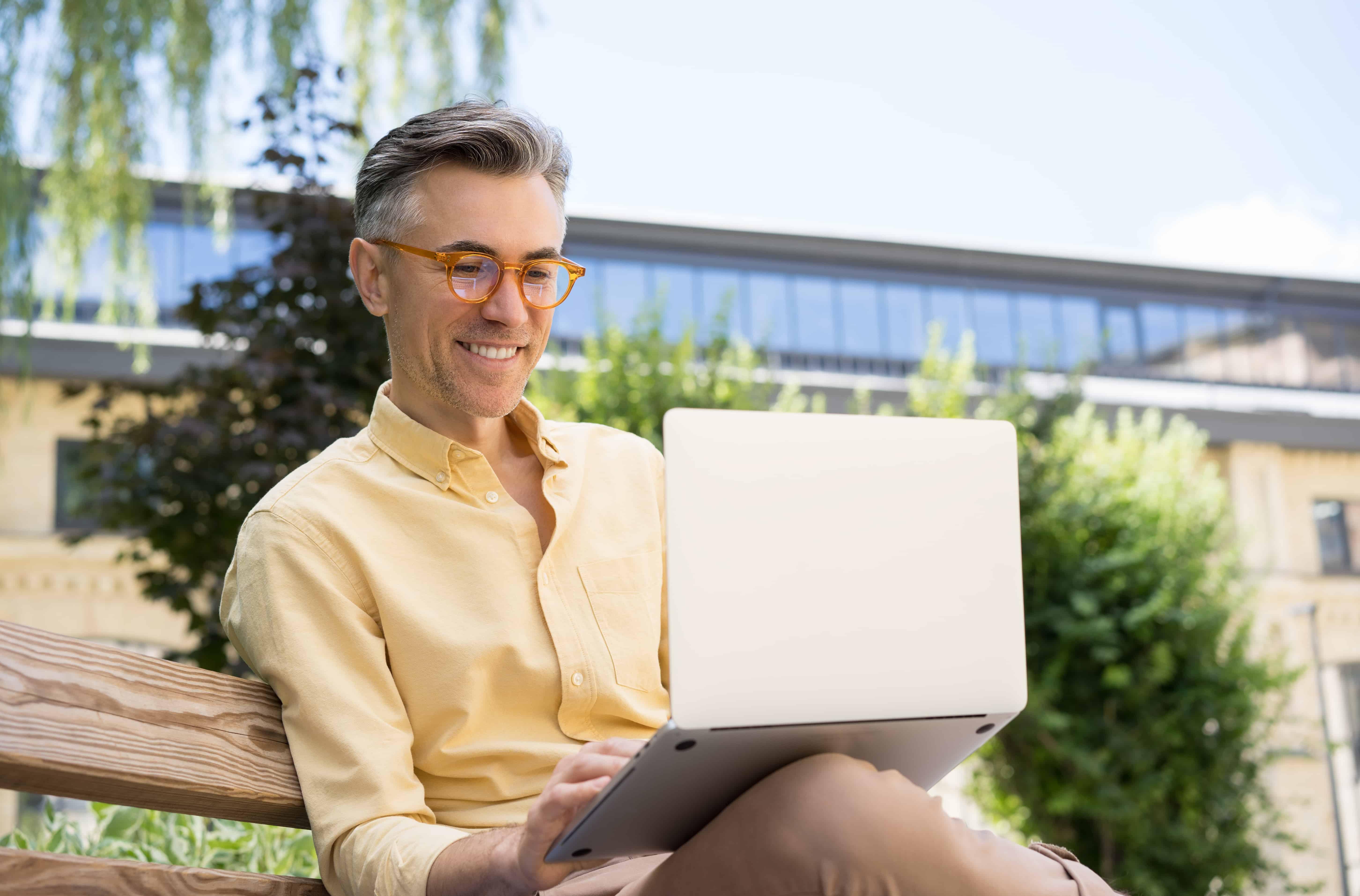 freelancer using laptop typing smiling mature man having video conference 1